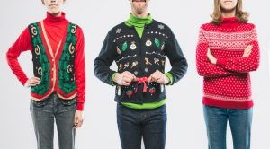 An image of a group of people wearing knit ugly Christmas sweaters with various bizarre patterns and decorations.