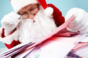 Image of Santa Claus in front of heap of letters reading one of them