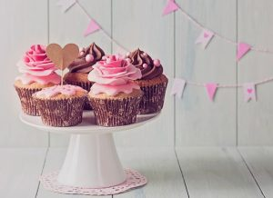Cupcakes with sweet rose flowers and a cakepick for text