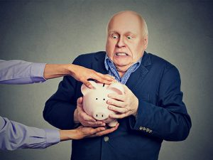 Picture of a guy holding on to his piggy bank