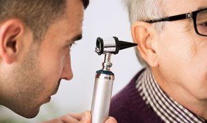 Audiologist looking into a patients ear.