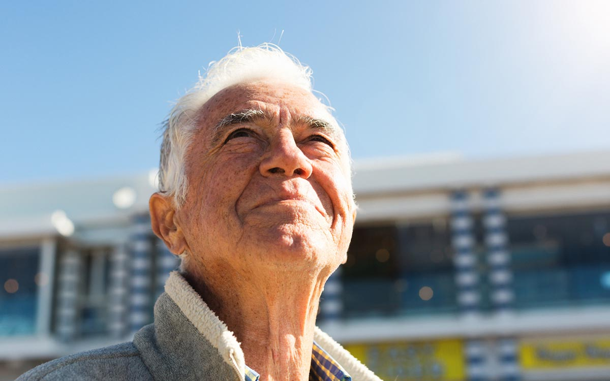 Smiling senior man looks up at sky, relaxed and contented