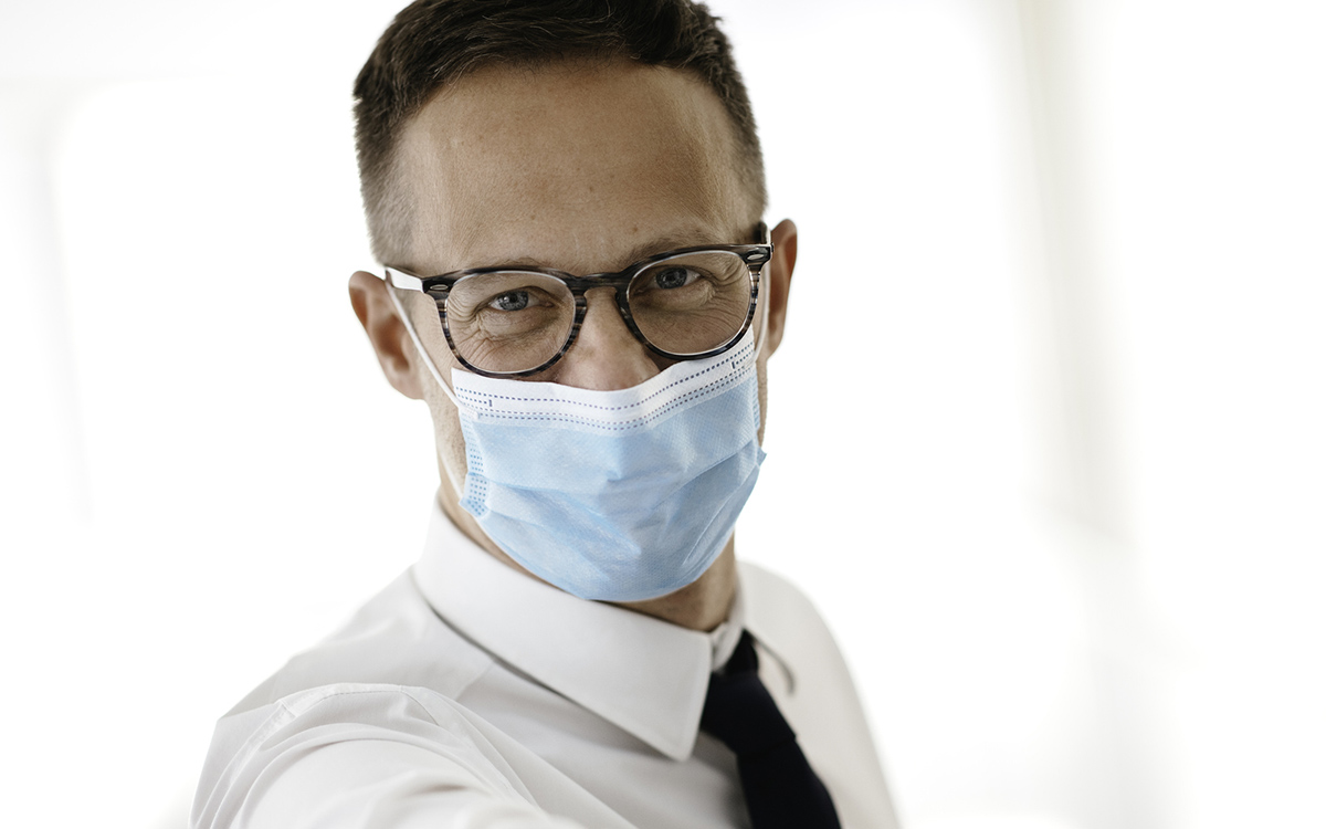 Close up portrait of man with mask on coping with running business.